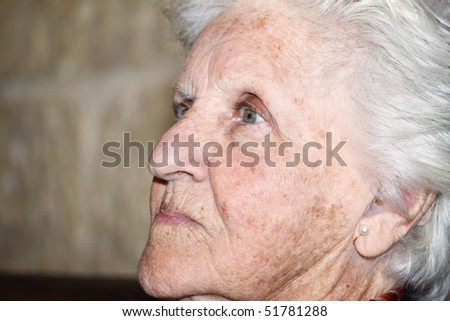 close-up profile portrait of an old woman showing aging skin with pigmentation and sun spots - stock photo