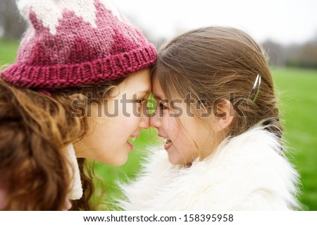 Close up profile portrait of two girl children sisters rubbing noses together while in a park during a cold winter day, having fun and smiling outdoors.