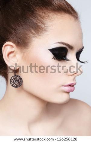 Close-up profile portrait of young beautiful woman with stylish make-up - stock photo