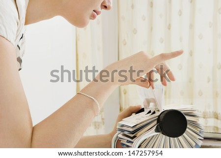 Close up profile view of a young business woman leaning forward on her office desk and picking a business card contacts details from her roller deck database, interior. - stock photo