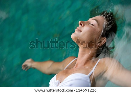 Close up profile view of a young woman floating in water while in a swimming pool on vacation.