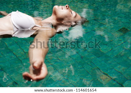 Close up profile view of a young woman floating in water while in a swimming pool on vacation. - stock photo