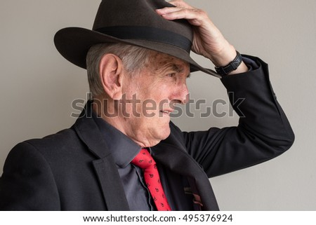 Close up profile view of older man in black suit and red tie with hand on hat
