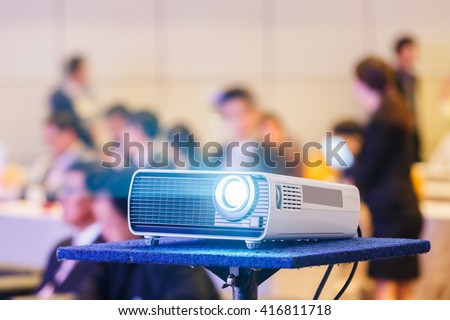 Close up projector in conference room with blurry people background - stock photo