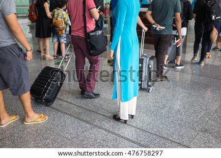 Close-up Queue of people in Noi Bai airport, Vietnam. Focus on female staff wearing Vietnamese traditional long dress Ao Dai
