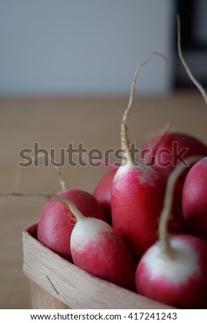close up radish in a wooden basket in natural light, soft focus