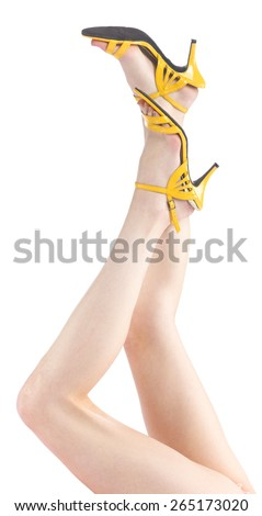 Close up Raised Sexy Woman Legs with Flawless Skin, Wearing Simple Yellow Shoes, Isolated on White Background. - stock photo