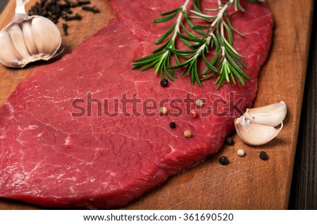 Close up raw beef meat on a cutting board with a sprig of rosemary, garlic and peppercorn. Top view with copy space - stock photo