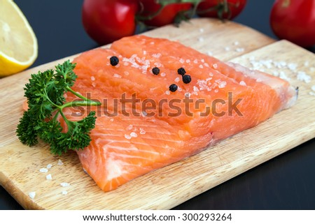 close-up raw salmon fillet with salt, pepper and parsley on a wood board