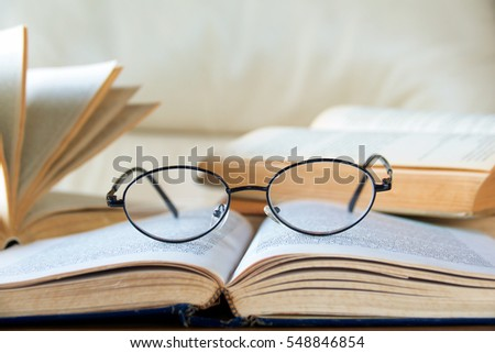 Close up reading glasses with vintage book on table