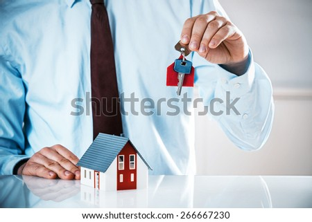 Close up Realty Male Agent at the Table Holding a House Key Up with Miniature Model House. - stock photo