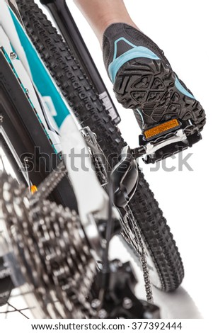 Close up rear view cyclist pedalling mountain bike isolated on white background.Studio shot.