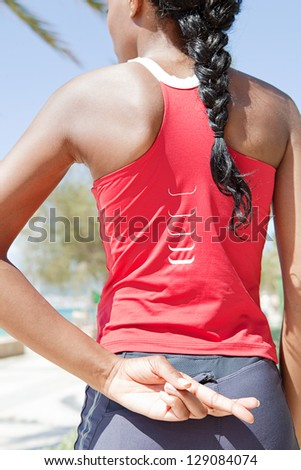 Close up rear view of a black woman standing against a blue sky after exercising, keeping her fingers crossed behind her back for good luck. - stock photo