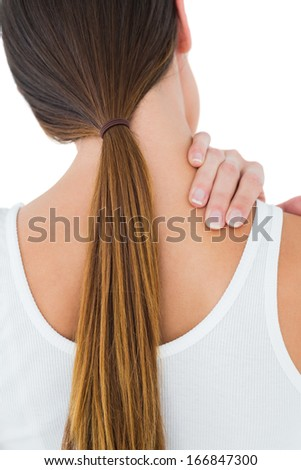 Close-up rear view of a casual young woman suffering from neck ache over white background