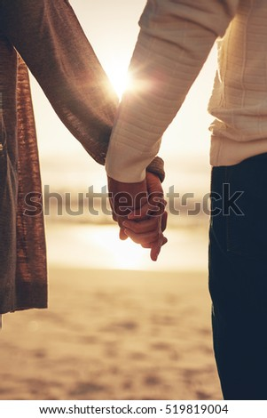 Close up rear view of a romantic senior couple holding hands against sea at sunset.