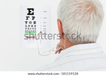 Close-up rear view of a senior man looking at eye chart at medical office - stock photo