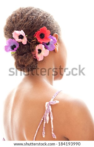 Close up rear view of a young african american black woman wearing flowers on her hair with perfect skin and beautiful shoulders, isolated on a white background. Beauty and care lifestyle.