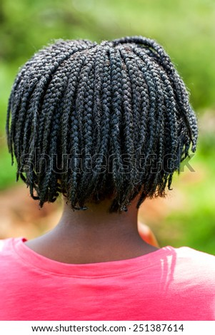 Close up rear view of African girl showing braided hairstyle outdoors. - stock photo