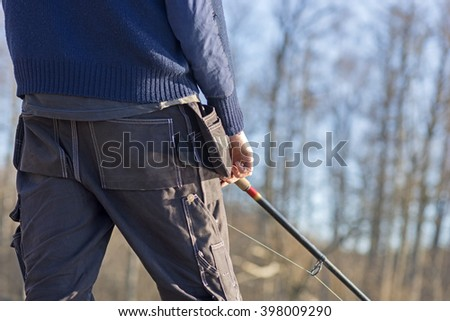 Close up rear view of man with fishing rod in early spring  - stock photo