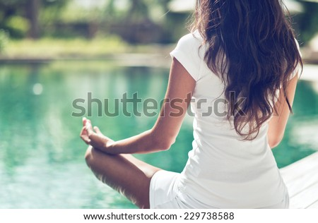 Close up Rear View of Slim Woman Meditating in a Lotus Yoga Position at the Poolside - stock photo