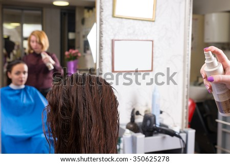 Close Up Rear View of Stylist Spraying Product onto Wet Hair of Brunette Female Client Seated in Salon Chair with Blurred Mirror Reflection in Background