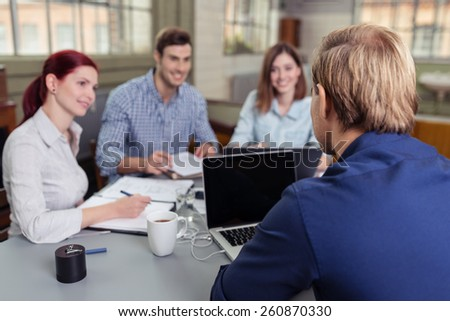 Close up Rear View of Young Blond Man Discussing to the Group at the Table. - stock photo