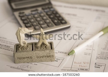 close up received and confirmed rubber stamp on office document with pen and calculator
