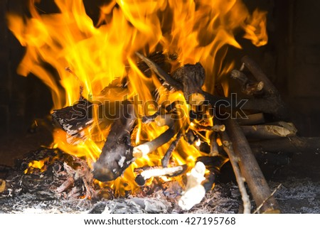 Close-up red and yellow flames in the fire of logs on the brick wall background - stock photo