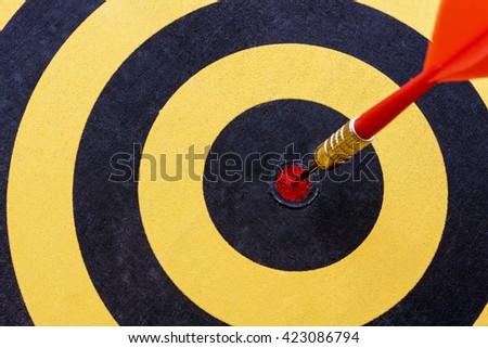 Close up red dart target with arrow hitting on bullseye of dartboard - stock photo