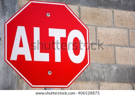 "close up red stop sign in Spanish ""alto"" fronting brick wall"