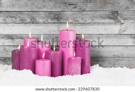 Close up Red Violet Lighted Candles for Christmas Decorations on the Snow with Vintage Wooden Wall Background. - stock photo