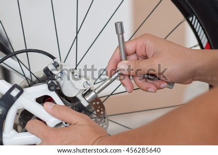 close up repairing a bicycle wheel  with tools - stock photo