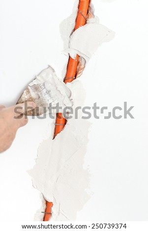 Close up Repairman Covering the Corrugated Cable Duct on the Wall with White Cement. - stock photo
