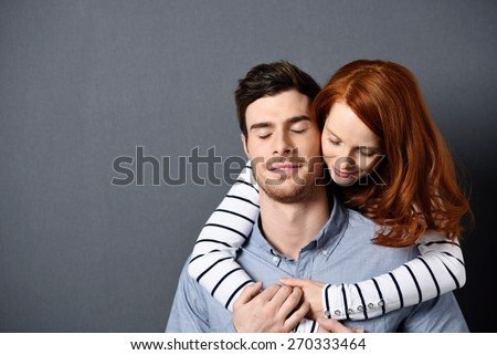 Close up Romantic Sweethearts - Pretty Girlfriend Hugging her Handsome Boyfriend From the Back with Both Eyes Closed. Isolated on Gray Background with Copy Space. - stock photo