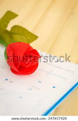 Close up Rose and calendar on wooden floor