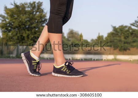 Close up runner legs on athletic track - stock photo