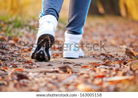 Close-up running feet in trainers of female runner. Healthy lifestyle, fitness, jogging, active, young concept.
