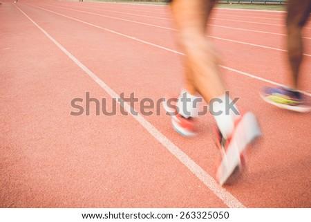Close up Running track with blur of runner feet in stadium - stock photo