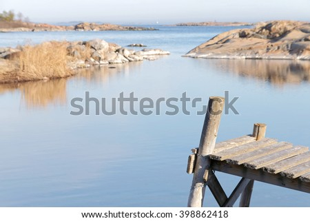 Close up rural small wooden bridge, coast and islands a sunny day during spring time in scandinavia. Short depth of focus - stock photo