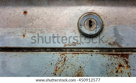 Close up rusty key hole of rolling steel door. Need to abstract by something wreck and unable to open