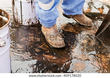 close up safety boot. worker cleaning crude oil contaminated on floor. waste management - stock photo
