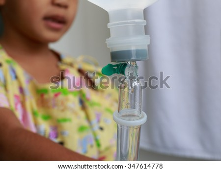 Close up saline IV drip for child's patient and blurred patient's child background.Pediatric care unit and medical concept. - stock photo