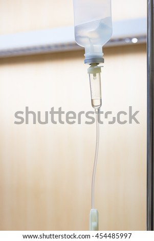 Close up saline solution drip for patient and infusion pump in hospital, with copy space wooden wall background at luxury VIP room.