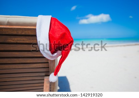 Close-up santa hat on chair longue on tropical caribbean beach - stock photo