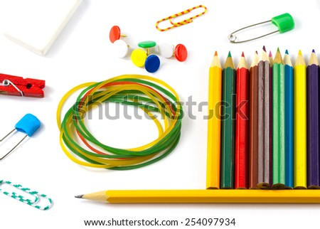 Close-up school supplies: colored pencils, paper clips, pencil sharpener, stationery gum, small clothespin, colored pins, pencil isolated on white background - stock photo