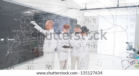 close-up  seen trough a transparent board in a chemistry lab of people analyzing information - stock photo