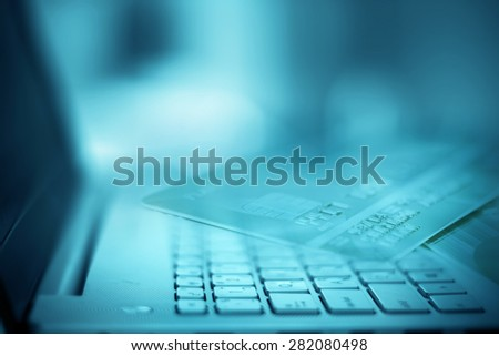 Close up selective focus of  the silver laptop computer with filtered by part of credit card - stock photo