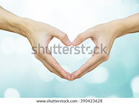 close up selective focus on man hands make heart over blurred bright blue color with bokeh light background:shallow man hand making heart-shape for showing healthy life:happy good healthy concept.  - stock photo
