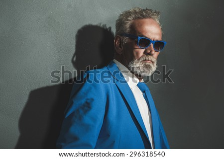 Close up Senior Bearded Man Wearing Blue Elegant Fashion with Sunglasses, Standing Against the Gray Wall with his Shadow. - stock photo