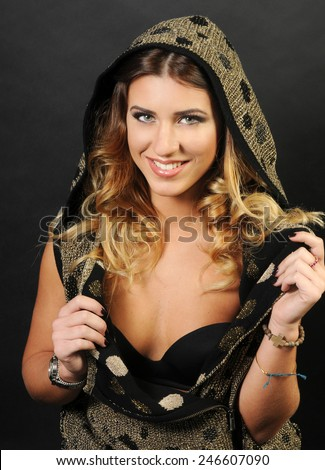 close up sensual portrait of a beautiful smiling caucasian girl with long curly hair wearing Golden vest with black polka dots and showing her black lingerie - stock photo